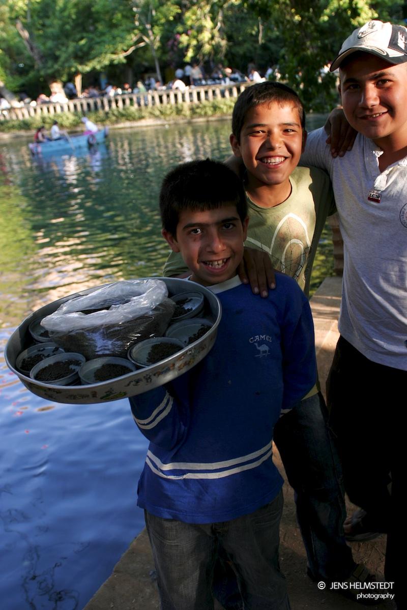 Kinder verkaufen Fischfutter am Karpfenteich in Urfa